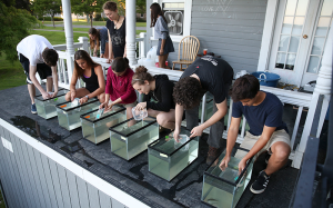 Dr. Meghan Brown and Poughkeepsie Day School students adding BRS prey to yellow perch experimental tanks. Feeding rate experiments were run under natural light conditions around twilight, a period of high BRS and fish feeding activity. Students (from left to right): Back row: Kate McKeon, Ellie Stapylton, Sonomi Oyagi, Front row: Chris Canfield, Julia Roellke, Meghan Brown, Mia Foucek, Jesse Held, Matt Warren. Photo credit: Kevin Colton.